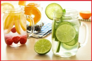 Detox water with various types of fresh fruit and vegetables in mason jars on a table
